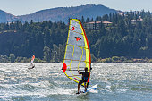 Underwood, Washington, USA - July 21, 2015: A windsurfer using a Realwind brand sailboard on a wind blown Columbia River near the shore in Washington State. This includes blue reflective water and an Oregon forested hill background near Hood River Oregon on the other side of the river. On the hill can be seen the backside of the Columbia Gorge Hotel. The Columbia Gorge Hotel is a historic landmark along Interstate 84 in Oregon. The Windsurfer is seen from the back in a wetsuit. A second windsurfer can be seen farther out in the water.