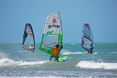 Three windsurfers sail the waves of a turquoise sea. The waves are small on the beach of Vila de Jeriocoacoara in northeastern Brazil. This beach is very popular with beginning or advanced windsurfers.