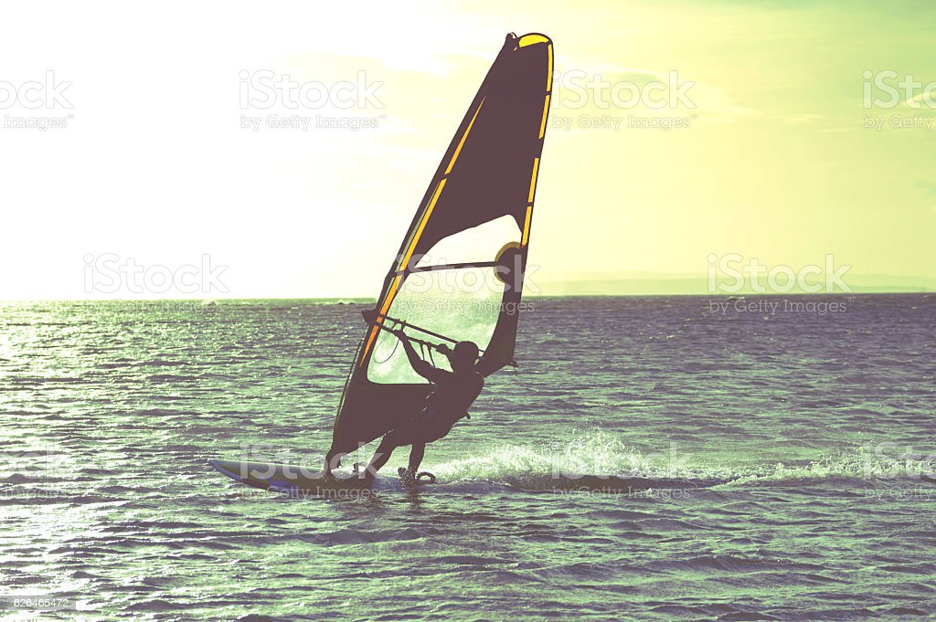 Windsurfer sailing at sunset, West Wittering stock photo