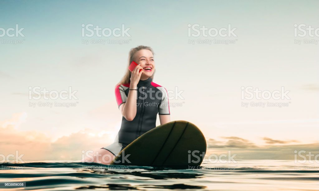 Windsurfer sitting on board and talks by phone - Royalty-free Adult Stock Photo
