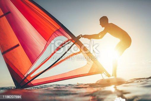 Windsurfer uplift sail for windsurf sailing on sunset sea.