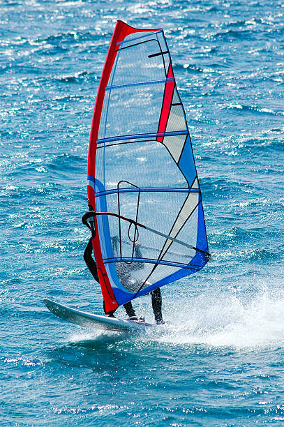 Windsurfer with translucent red and blue sail stock photo