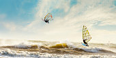 Windsurfers enjoying the waves on a stormy day in the Netherlands.