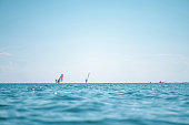 Windsurfers in the sea on sunset on horizon. Close up of sea wave, low angle view. Selective focus, bokeh