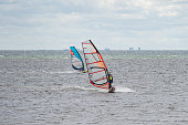 Malmo, Sweden - July 12, 2020: On a windy day many people take the opportunity to do watersports. Windsurfers gather near Lomma beach to practice their windsurfing skills