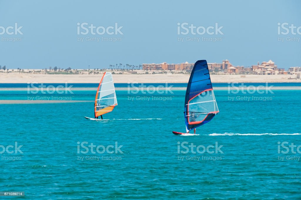 Windsurfers, with orange and blue sails crossing right to left with waterfront buildings behind stock photo