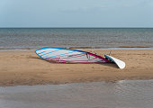 A single wind surfing board on a sandy beach with the sea in background