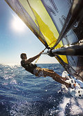 Windsurfing in sea with splashing water. Perspective from behind on sail towards the surfer.