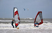 Netherlands. Scheveningen. August 10, 2019. Two windsurfers on a stormy day with big waves.