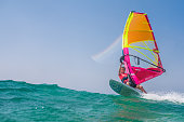 Young woman windsurfing on sea with board and colourful sail.
