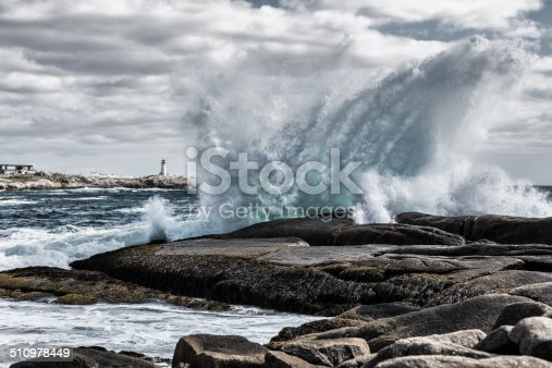 An offshore storm sends heavy windswept ocean surf/breakers crashing over the coastal shoreline rocks at Peggy's Cove, Nova Scotia, Canada. Peggy's Cove lighthouse is in the background.