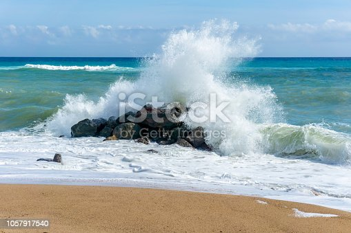 Waves crashing over rocks on edge of beach in Spain, Europe