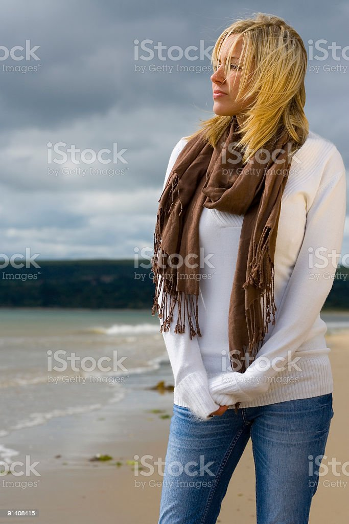 Windswept & Thoughtful Beautiful Young Woman on Stormy Beach royalty-free stock photo
