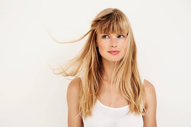 windswept young woman with blond hair - sarı saç stok fotoğraflar ve resimler