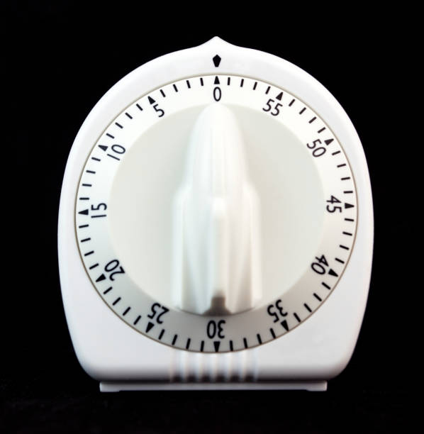 Wind-up Kitchen Timer Traditional white kitchen wind up egg timer on a black background. timer stock pictures, royalty-free photos & images