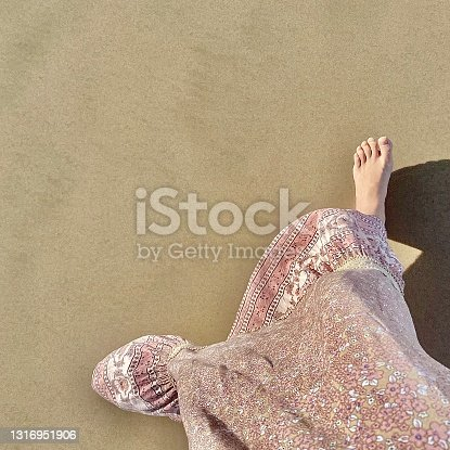 Girl's foot splashes sea water. Woman's leg on the background of the sea