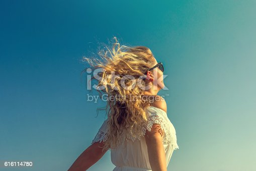 windy in hair dreamy girl with sunflare on beach