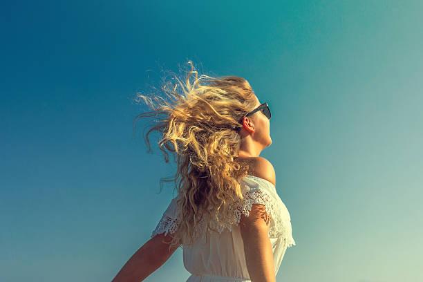 windy in hair dreamy girl with sunflare on beach - chica rubia espaldas fotografías e imágenes de stock