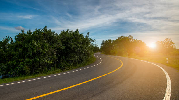 windy road through forest lead to sunset - road map stock photos and pictures