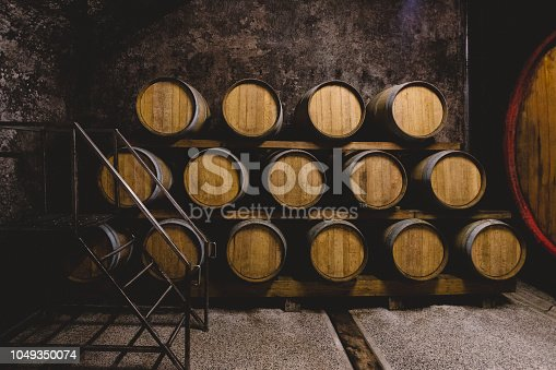 Barrels of wine stored inside of cellar deep underground.