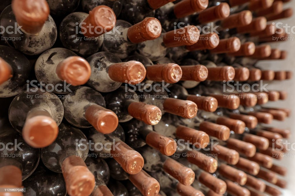 Wine aging process. Wine bottles aging, covered in dust and mold, in...