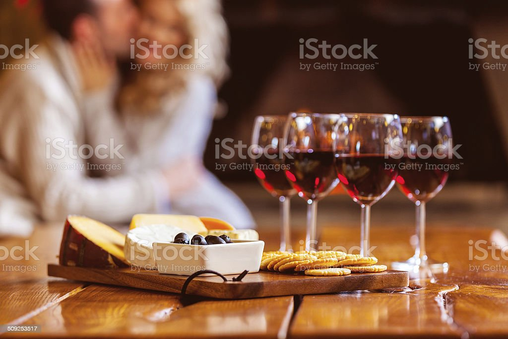 Wine and cheese Focus on four red wine glasses and chesse platter with couple in the background. Adult Stock Photo