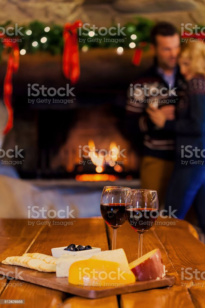 Wine and cheese Focus on two red wine glasses and chesse platter with couple standing by fireplace in the background. Adult Stock Photo
