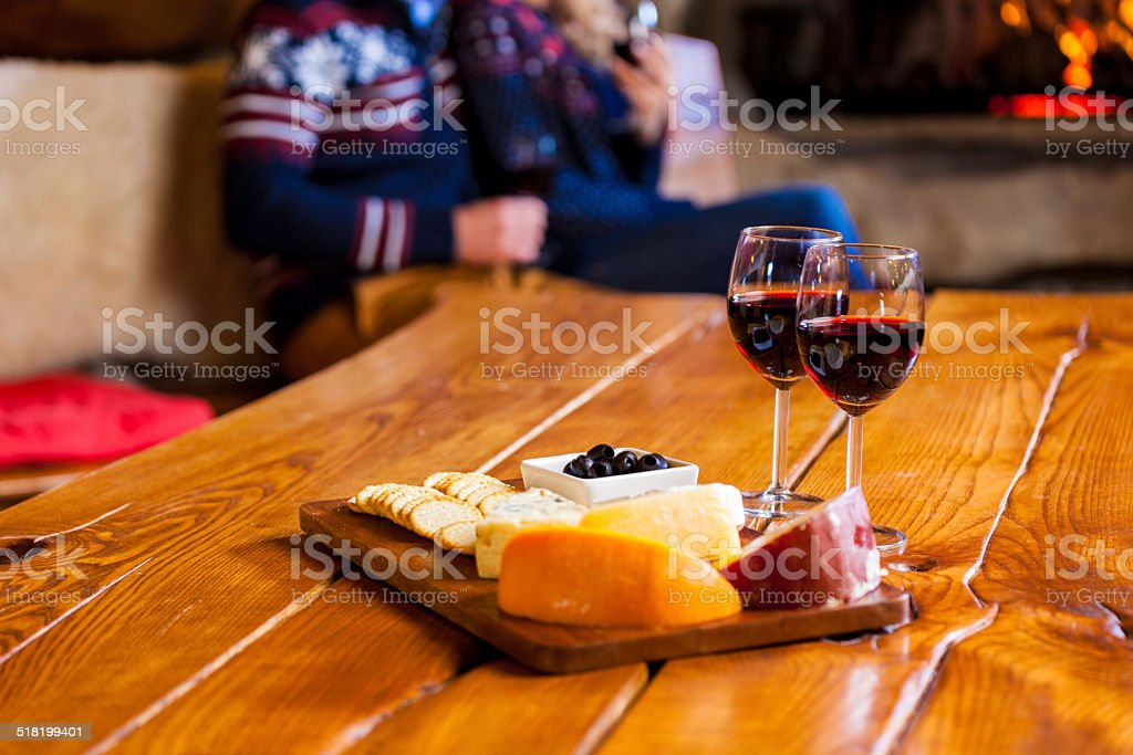 Wine and cheese Focus on two red wine glasses and chesse platter with couple sitting by fireplace in the background. Adult Stock Photo