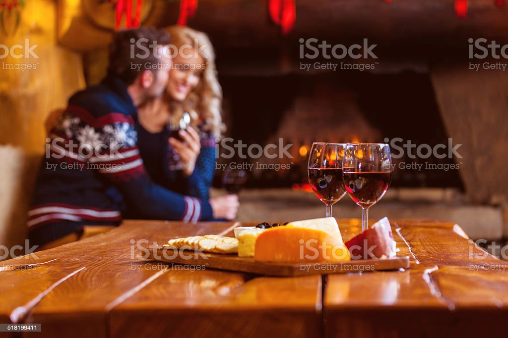 Wine and cheese Focus on four red wine glasses and chesse platter with couple flirting by fireplace in the background. Adult Stock Photo