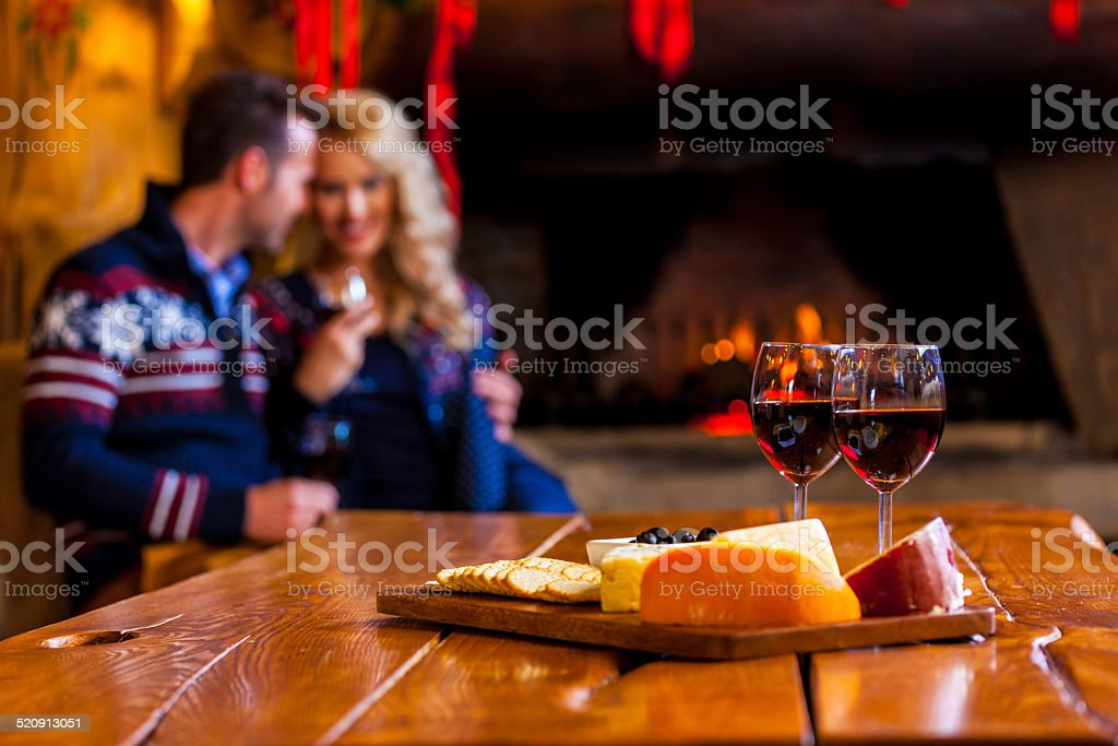 Wine and cheese Focus on four red wine glasses and chesse platter with couple sitting by fireplace in the background. Adult Stock Photo