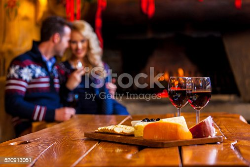 Focus on four red wine glasses and chesse platter with couple sitting by fireplace in the background.
