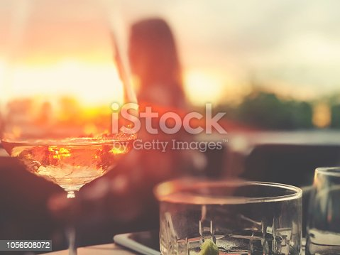 Wine and cocktails on a table at a bar. There is white wine with a fruit cocktail. Backlit at sunset with lens flare