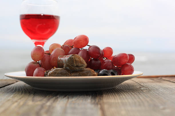 wine and stuffed vine leaves with grapes stock photo
