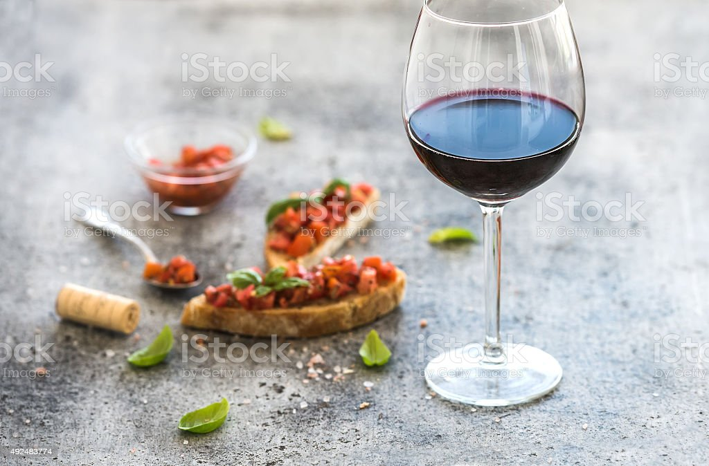 Wine appetizer set. Glass of red wine, brushettas with fresh stock photo