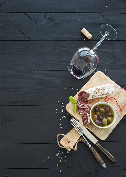 mit wein und appetithäppchen. glas rotwein, französische salami und - salami vorspeise stock-fotos und bilder