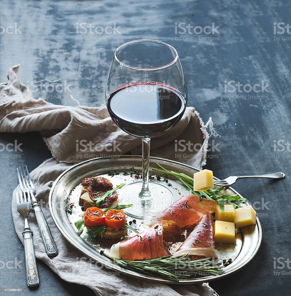 Wine appetizer set. Glass of red wine, vintage dinnerware stock photo