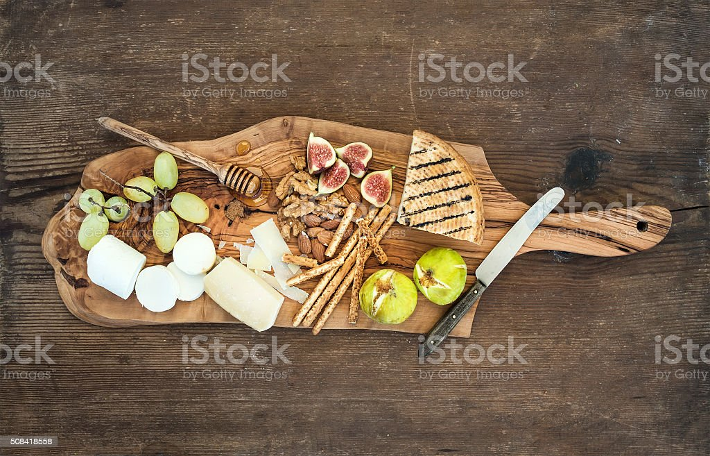 Wine appetizers set: cheese selection, honey, grapes, almonds, walnuts, bread stock photo