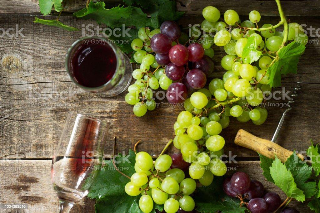 Wine background. Red wine in glasses, bottle, grapes on vintage...