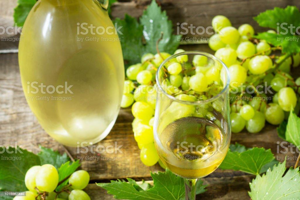 Wine background. White wine in glasses, bottle, grapes on vintage...