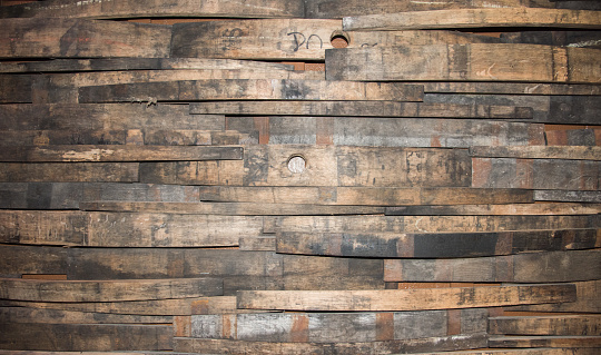 Closeup of a portion of a wall built up with wine barrel wooden strips in a variety of widths.