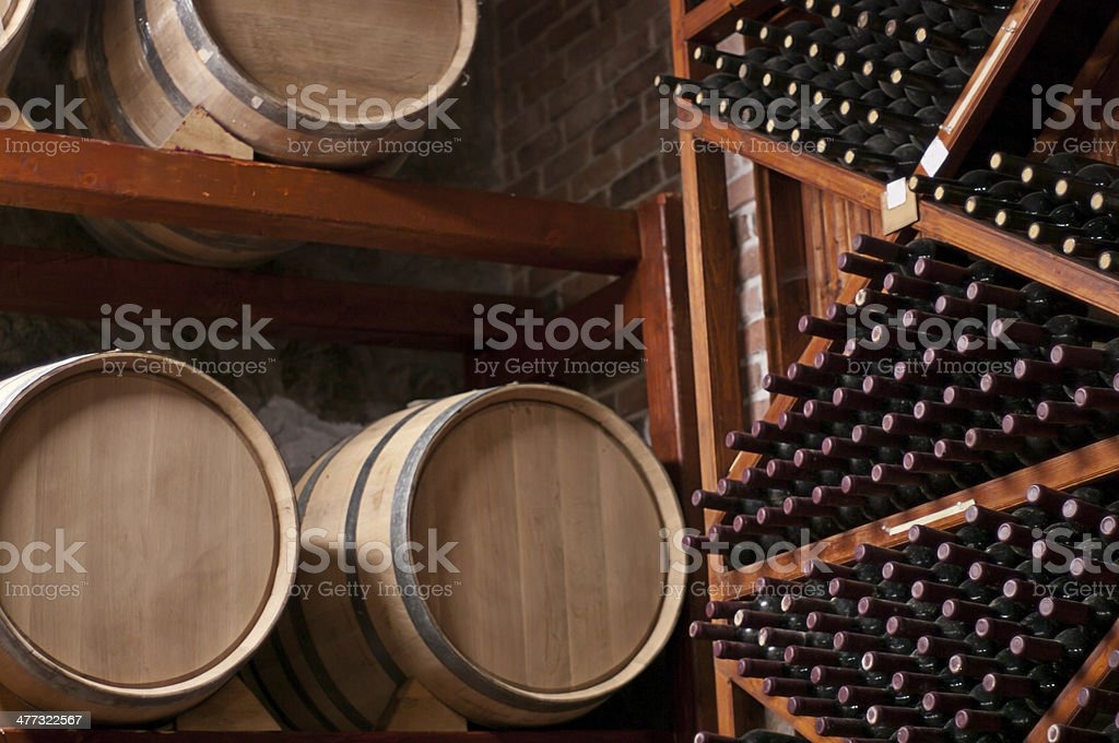 Wine Barrels and bottles on shelf in a Cellar stock photo