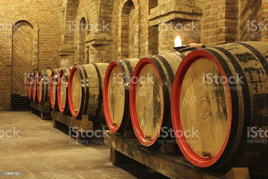 Wine barrels in a cellar with a lighting candle royalty-free stock photo