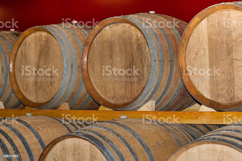 Wine Barrels Stacked Against Bright Red Wall. Shot in Italy.