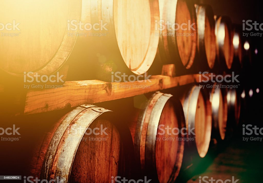 Wine barrels stacked in cellar in mellow golden light stock photo