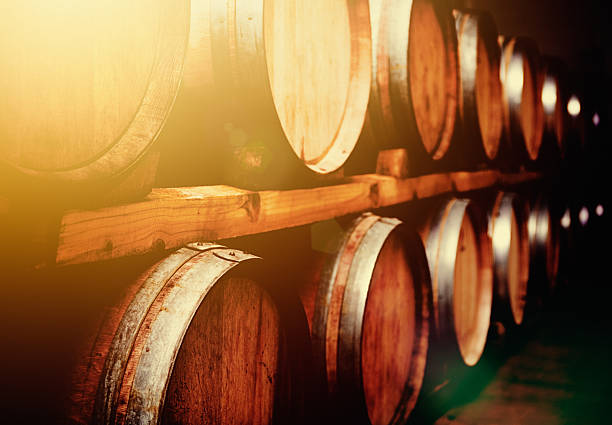 wine barrels stacked in cellar in mellow golden light - bierfass stock-fotos und bilder