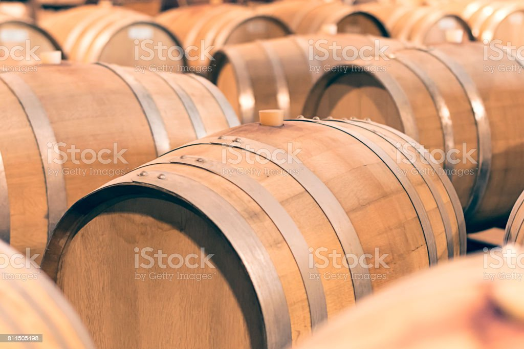 Wine barrels stacked in the  cellar of the winery. stock photo