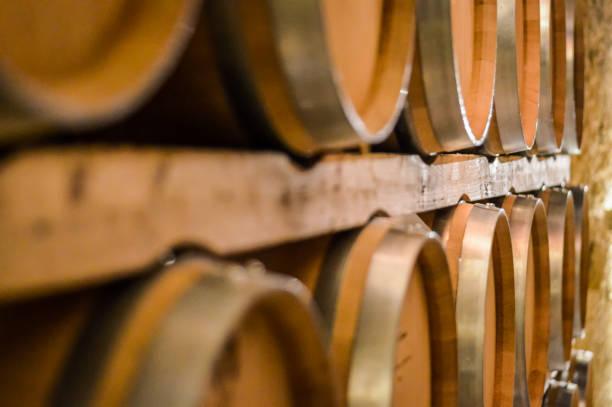 wine barrels stacked in winery cellar - weinkeller bauen stock-fotos und bilder