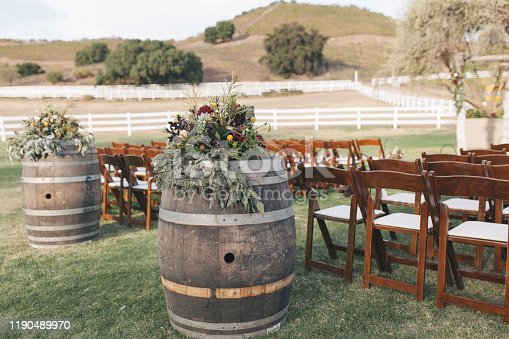 Outdoor ceremony area decorated with empty wine barrels, boho styled floral arrangement, pine cones, chairs and mountains on the background