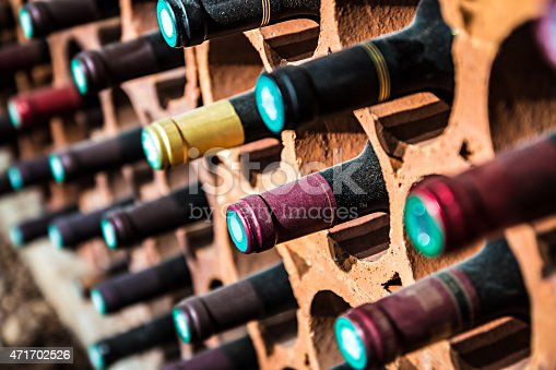 Selective focus of wine rack on wall in brick material full, to store red wine bottle in a row in cellar, cool and in good conditions.Some of those are old wine bottle with dust.