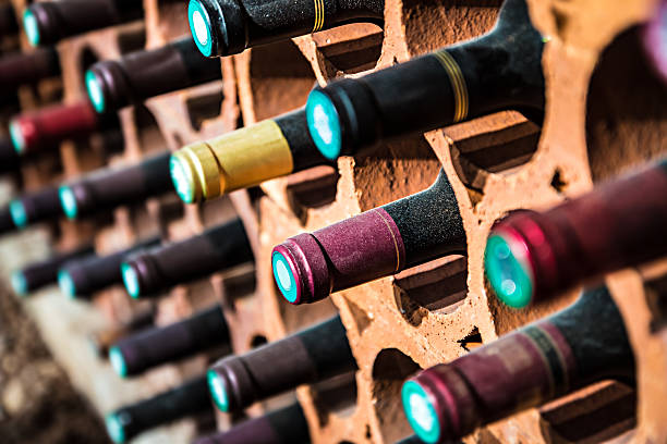 Wine bootles from cellar in selective focus Selective focus of wine rack on wall in brick material full, to store red wine bottle in a row in cellar, cool and in good conditions.Some of those are old wine bottle with dust. french culture stock pictures, royalty-free photos & images